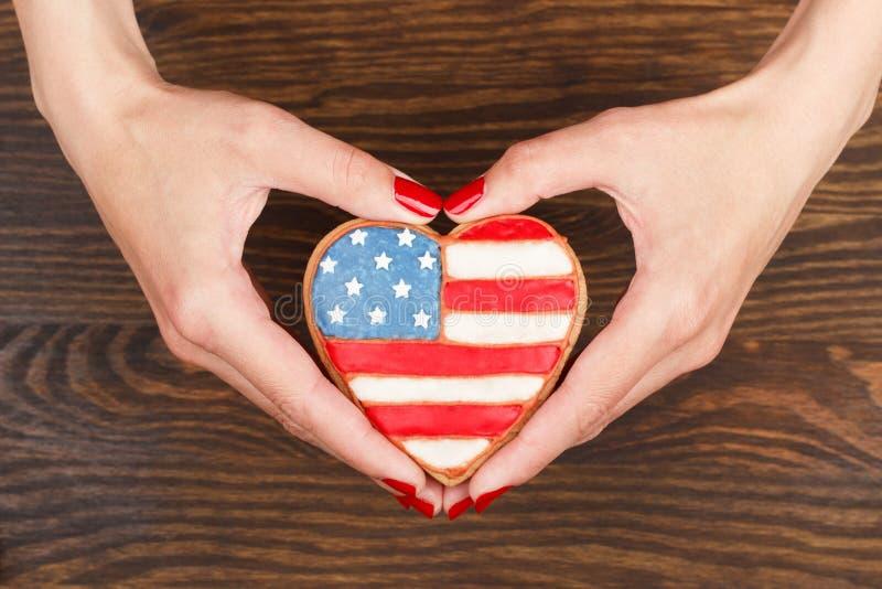 Galleta con colores patrióticos americanos en las manos fotos de archivo
