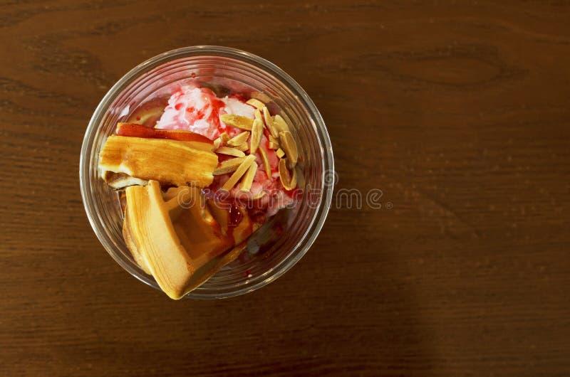 Galleta con helado de fresa en vidrio en la tabla de madera fotografía de archivo