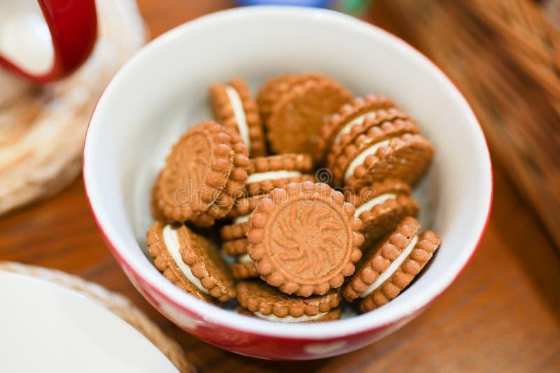 Galleta de la galleta con el fondo de congelación blanco en la placa blanca y roja en la tabla de madera marrón comida sabrosa pa imágenes de archivo libres de regalías