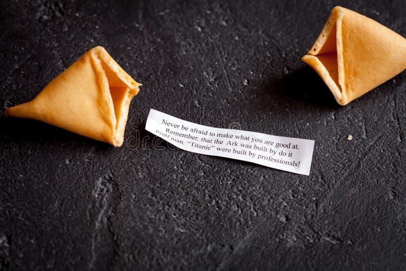 Galleta de la suerte china con la predicción en la opinión superior del fondo oscuro imágenes de archivo libres de regalías