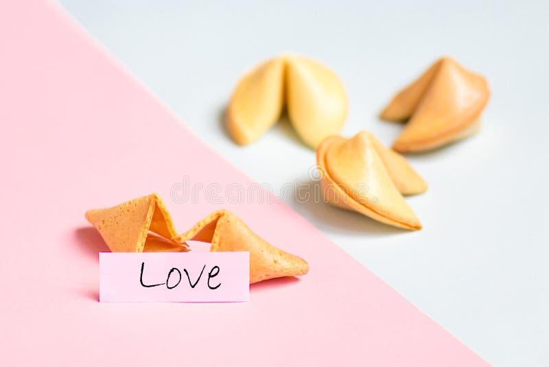galleta de la suerte en el rosa y el fondo azul, colores en colores pastel, predicción del amor foto de archivo