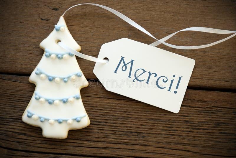 Galleta del árbol de navidad con la etiqueta de Merci imágenes de archivo libres de regalías
