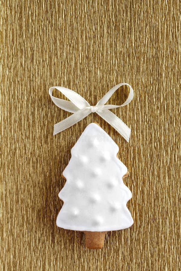 Galleta del árbol de navidad del jengibre en fondo del oro imagen de archivo
