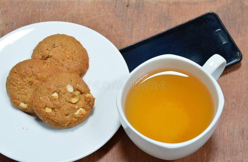 Galleta del cacahuete y taza de té con el teléfono móvil negro foto de archivo