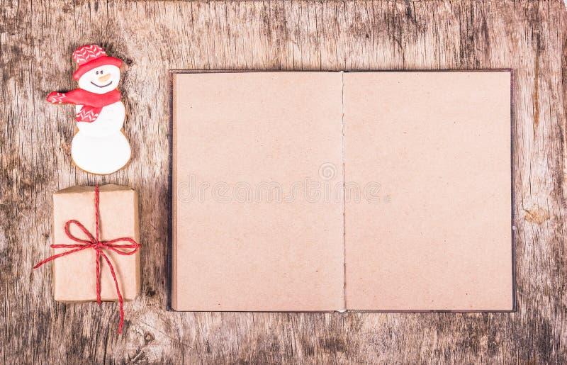 Galleta del jengibre bajo la forma de muñeco de nieve, regalo y libro Abra el libro con las paginaciones vacías fotografía de archivo libre de regalías