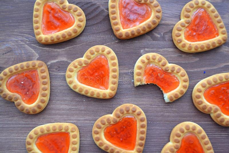 Galleta en la forma de corazón con el atasco rojo, fondo de la textura Concepto de las tarjetas del día de San Valentín del amor  imagen de archivo libre de regalías