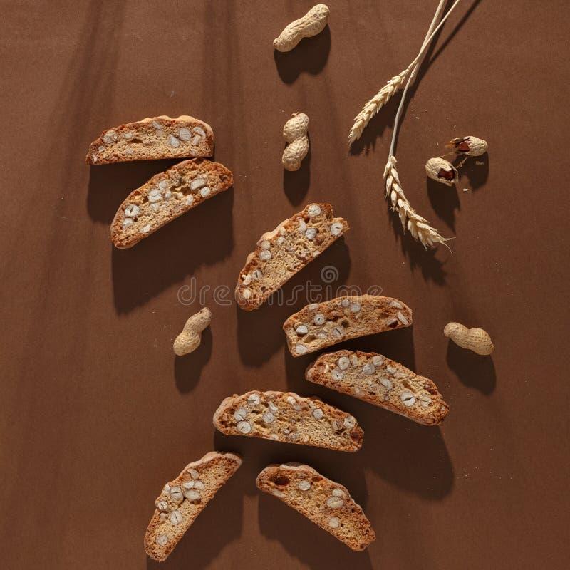 Galleta italiana del cantuccini con el relleno, el trigo y las nueces de la almendra en fondo marrón Visi?n superior fotografía de archivo