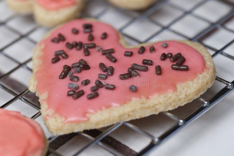 Galleta rosada del corazón de la tarjeta del día de San Valentín en el estante de enfriamiento imagenes de archivo