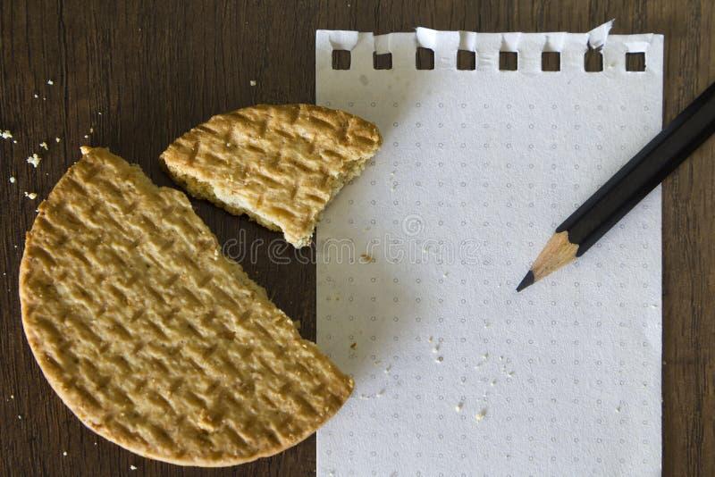 Galleta y papel y lápiz en blanco de nota foto de archivo libre de regalías