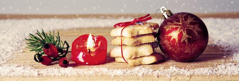 Galleta y vela de la Navidad en la tabla de madera foto de archivo