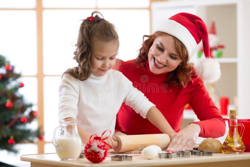 Galletas adorables de la Navidad de la hornada de la niña y de la madre imagenes de archivo