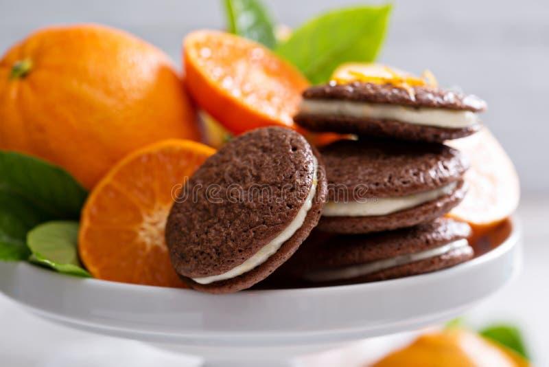 Galletas anaranjadas del chocolate con el relleno poner crema fotos de archivo