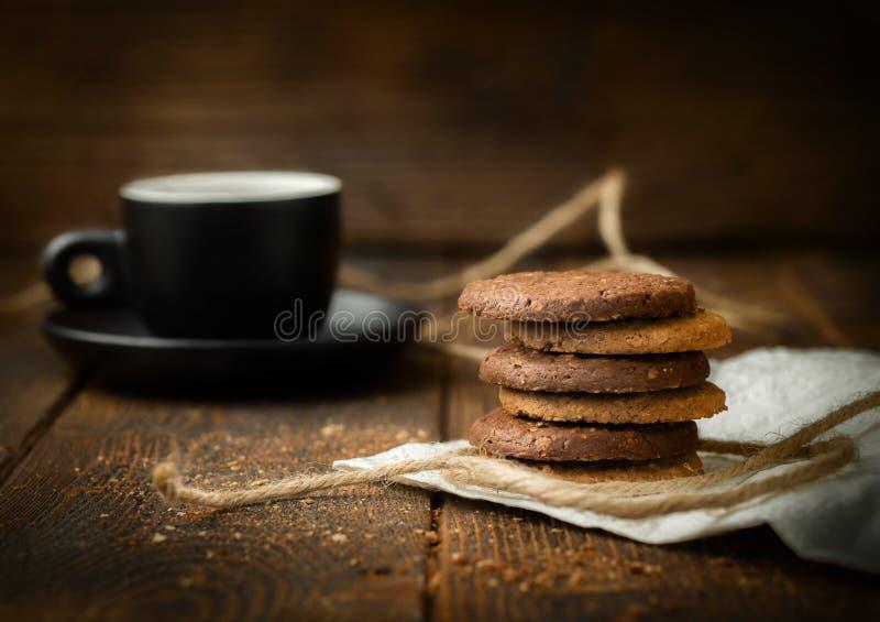 Galletas apiladas en fondo de madera oscuro con la taza de café foto de archivo