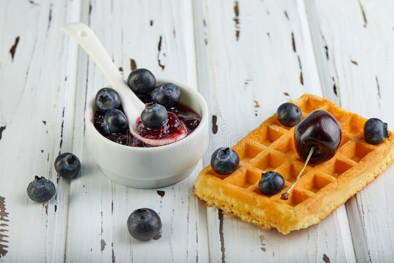 Galletas belgas del desayuno sabroso con los arándanos y el atasco poner crema azotados en un blanco de madera fotografía de archivo libre de regalías