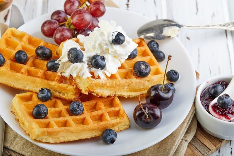 Galletas belgas del desayuno sabroso con los arándanos y el atasco poner crema azotados en un blanco de madera foto de archivo