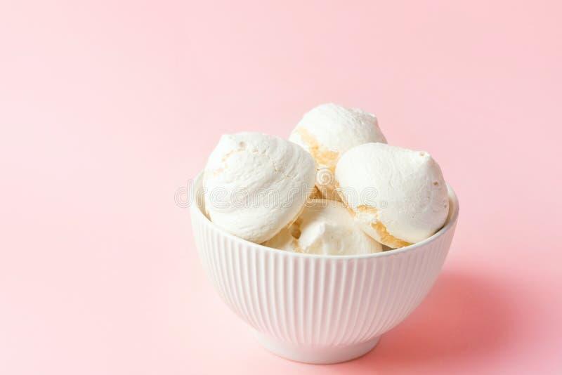 Galletas cocidas caseras del merengue en el cuenco de cerámica blanco del vintage en fondo rosa claro de la pendiente Postres sui imagen de archivo libre de regalías