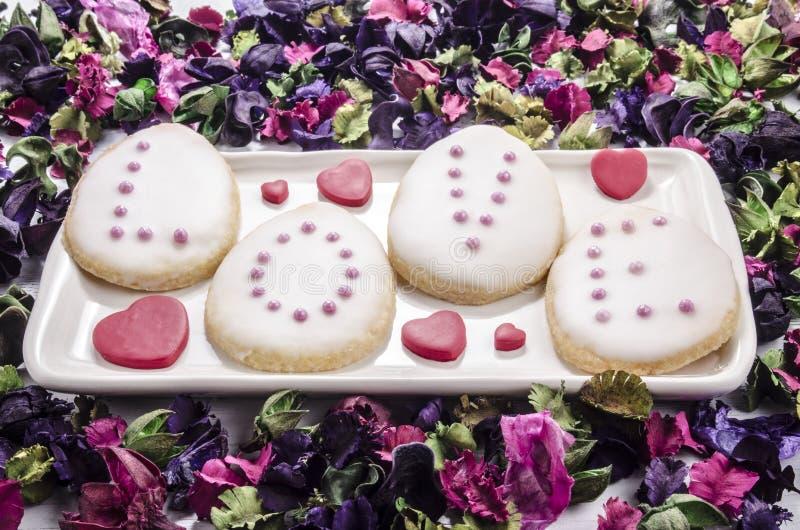 Galletas cocidas con helar y perlas rosadas fotos de archivo libres de regalías