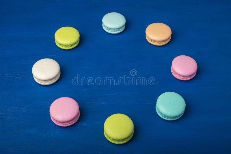 Galletas coloridas Apelmace el macaron o los macarrones en un fondo azul imagen de archivo libre de regalías