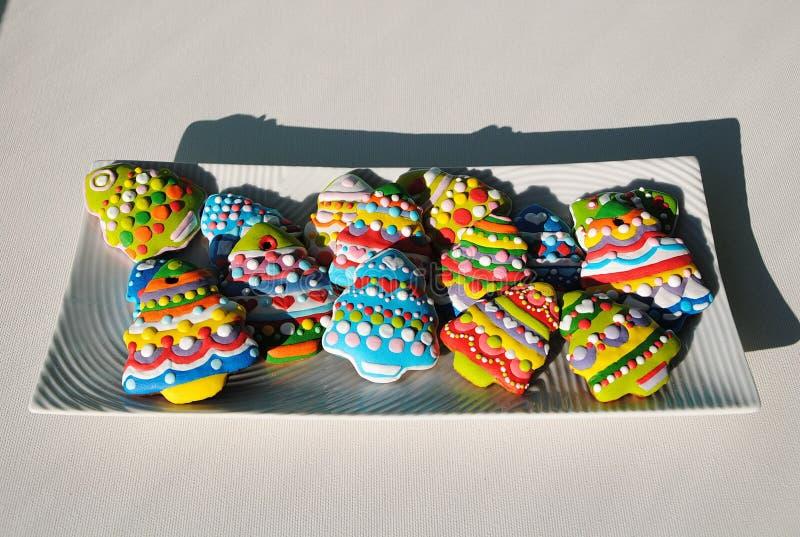 Galletas coloridas en un fondo blanco, galletas de los árboles de navidad de la Navidad adornadas para los niños imagen de archivo libre de regalías