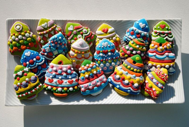 Galletas coloridas en una placa blanca, galletas de los árboles de navidad de la Navidad adornadas para los niños fotos de archivo
