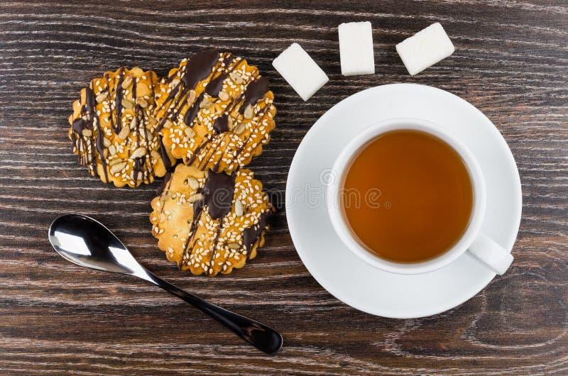Galletas con el chocolate y las semillas, azúcar, cucharilla, taza con té foto de archivo
