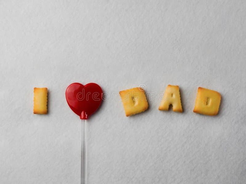 """Galletas con formas de la letra y una piruleta en forma de corazón roja, dispuesta en un  de Dad†del amor del """"I del mensaje imagen de archivo libre de regalías"""
