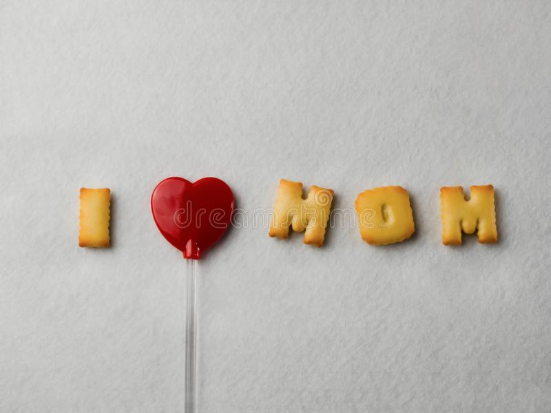 """Galletas con formas de la letra y una piruleta en forma de corazón roja, dispuesta en un  de Mom†del amor del """"I del mensaje imágenes de archivo libres de regalías"""