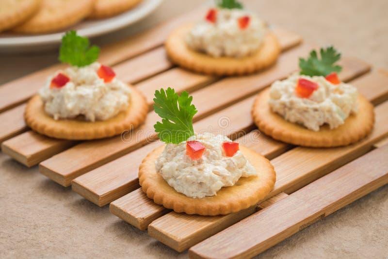 Galletas con la ensalada de atún en la placa de madera imagen de archivo libre de regalías
