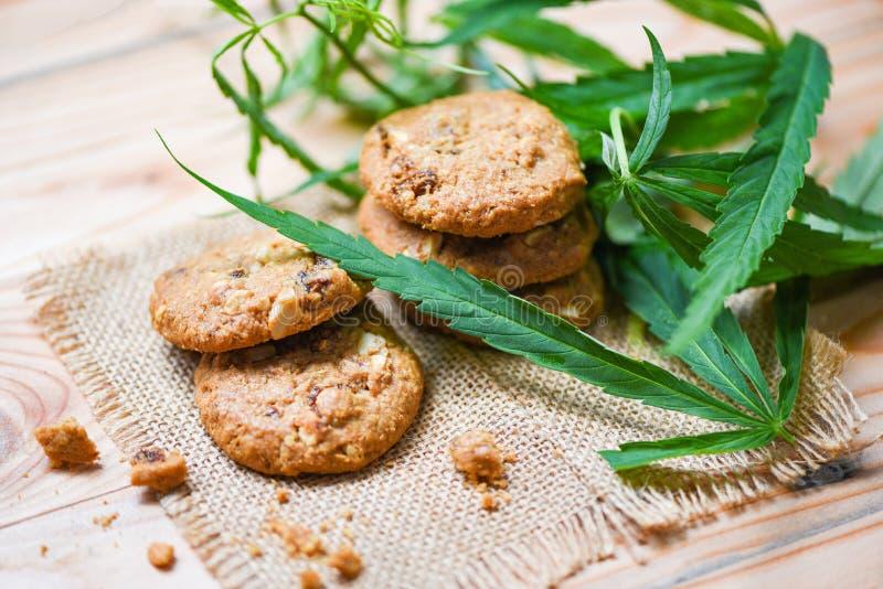 Galletas con la hierba de la marijuana de la hoja del cáñamo en el fondo de madera del saco - bocado de la comida del cáñamo para fotografía de archivo libre de regalías