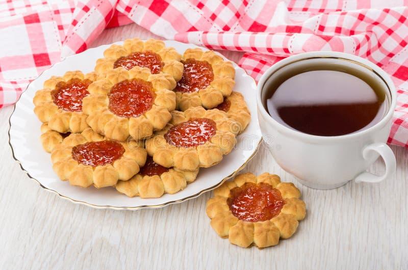 Galletas con la mermelada de fresa en la placa, taza de té fotos de archivo libres de regalías