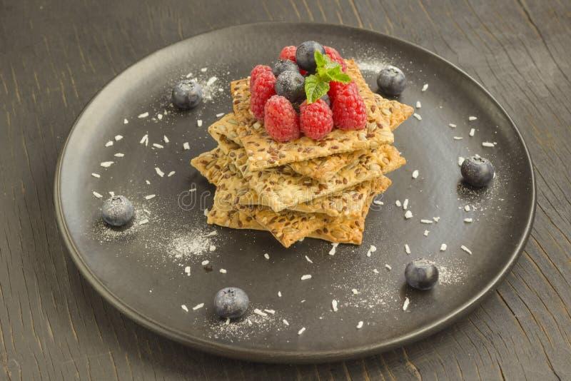 Galletas con los granos enteros Bayas de la frambuesa y del arándano en el top Placa negra, visión superior imagen de archivo
