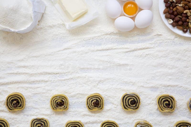 Galletas crudas con las semillas, las pasas y las nueces de amapola en la tabla de madera blanca Ingredientes para hacer las gall fotos de archivo libres de regalías