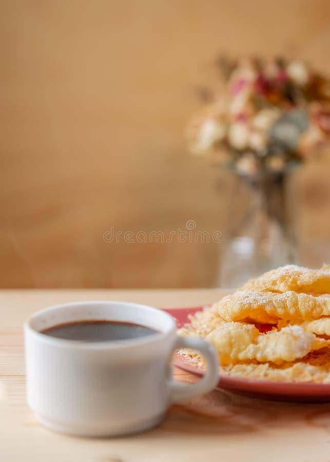 Galletas curruscantes Crackled con el az?car en una placa y una taza de caf? en una tabla de madera fotografía de archivo libre de regalías