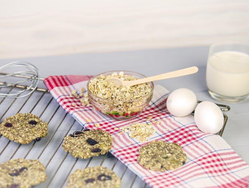 Galletas de harina de avena con las frutas secadas, semillas, arándanos en un estante de rejilla En fondo gris de madera con un v foto de archivo