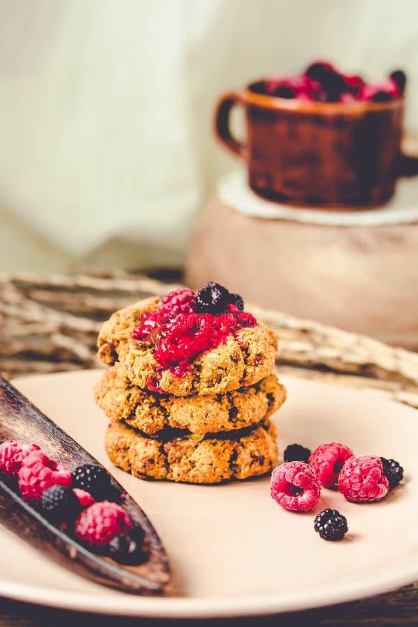 Galletas de harina de avena crujientes del vegano hecho en casa con el atasco de frambuesa y el caramelo de la fecha en un fondo  imágenes de archivo libres de regalías