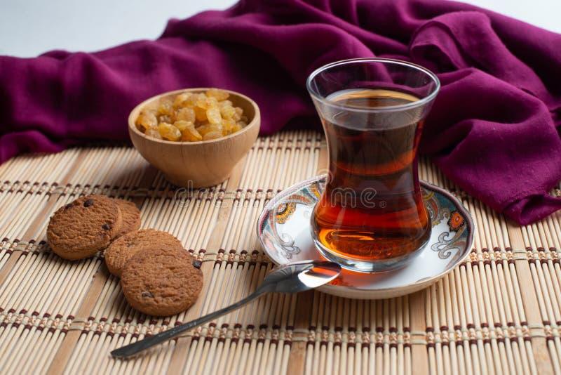 Galletas de harina de avena hechas en casa con una taza de té en viejo fondo de madera, una taza de té con la pasa, una taza de t foto de archivo