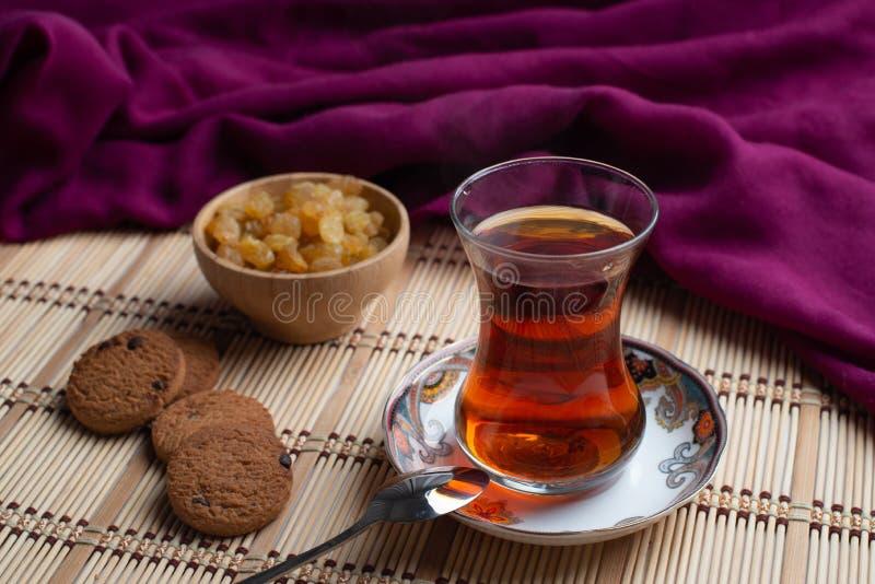 Galletas de harina de avena hechas en casa con una taza de té en viejo fondo de madera, una taza de té con la pasa, una taza de t imagen de archivo