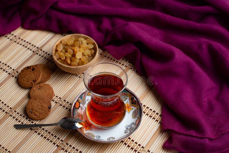 Galletas de harina de avena hechas en casa con una taza de té en viejo fondo de madera, una taza de té con la pasa, una taza de t fotos de archivo