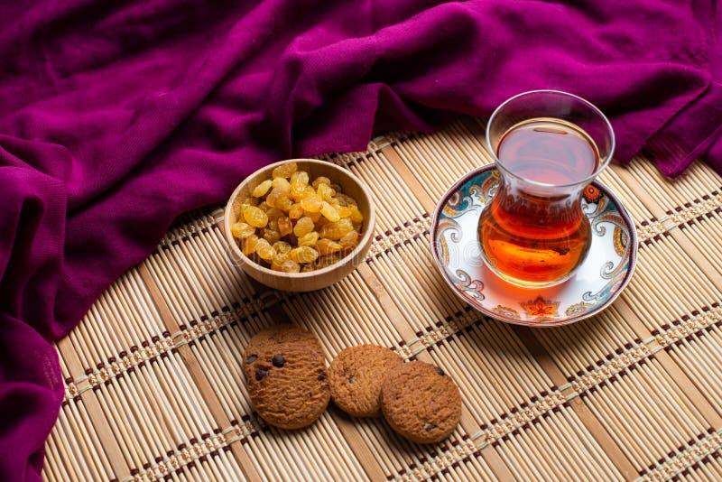 Galletas de harina de avena hechas en casa con una taza de té en viejo fondo de madera, una taza de té con la pasa, una taza de t fotos de archivo libres de regalías