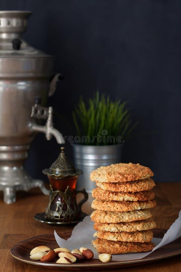 Galletas de harina de avena de la pila con las nueces y té negro en el samovar en una tabla de madera imágenes de archivo libres de regalías