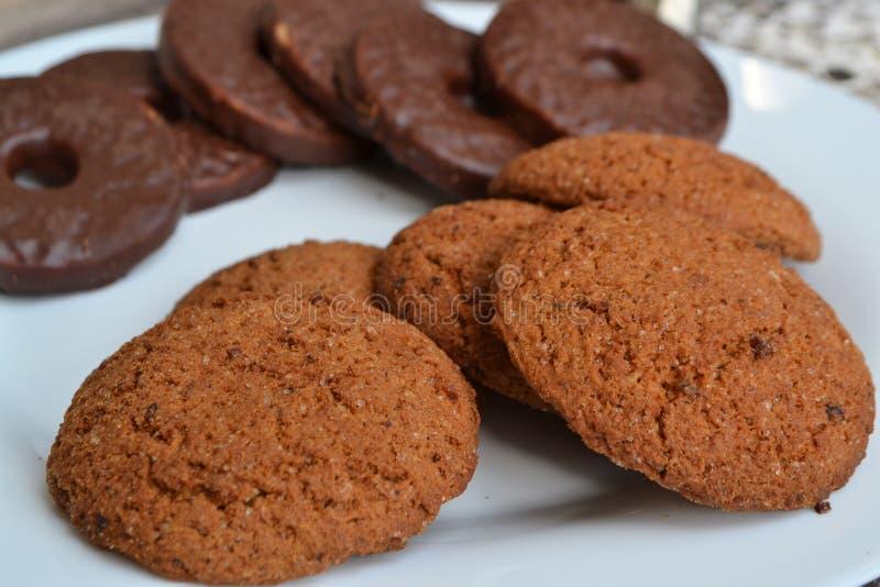 Galletas de la avena y bisquit del chocolate en una placa blanca imagen de archivo