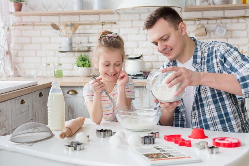 Galletas de la hornada del padre y de la hija con receta en la tableta digital imágenes de archivo libres de regalías