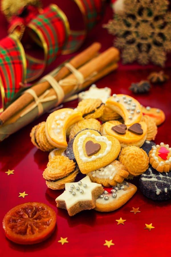 Galletas de la Navidad con la decoración festiva en el fondo rojo, ver foto de archivo libre de regalías