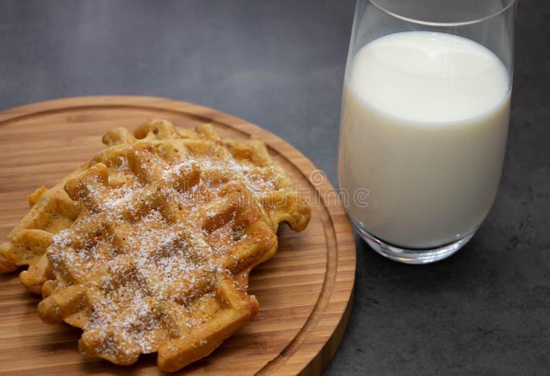Galletas de la zanahoria con el azúcar en polvo en un tablero de madera con un vidrio de leche Desayuno sano perfecto foto de archivo