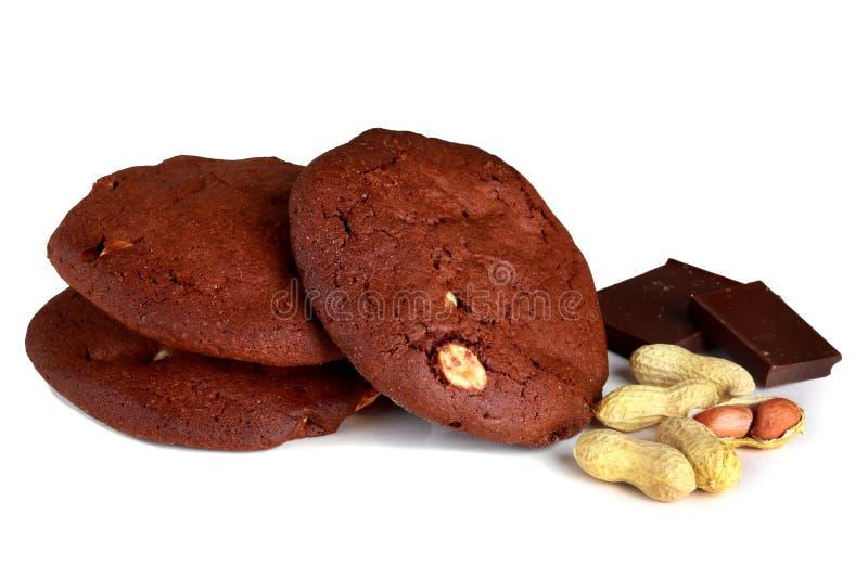 Galletas de las galletas del chocolate, con los cacahuetes aislados en el backg blanco foto de archivo