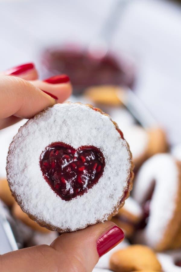 Galletas de lino con forma de corazón caseras con mermelada de frambuesa en la mano de mujer Cerrar El concepto del amor imagen de archivo libre de regalías