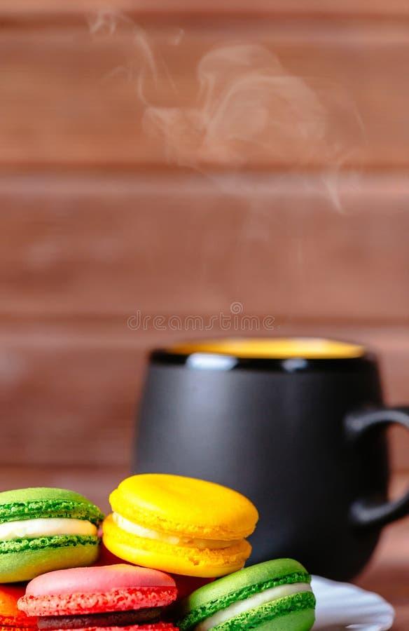Galletas de Macarons y bebida caliente imagen de archivo