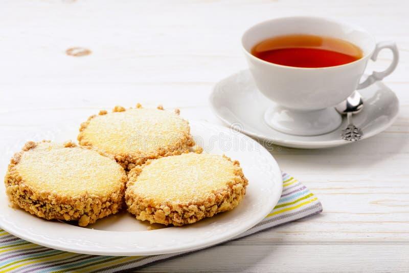 Galletas de mantequilla (alfajores) con caramelo y cacahuete y taza de té en fondo de madera fotos de archivo libres de regalías