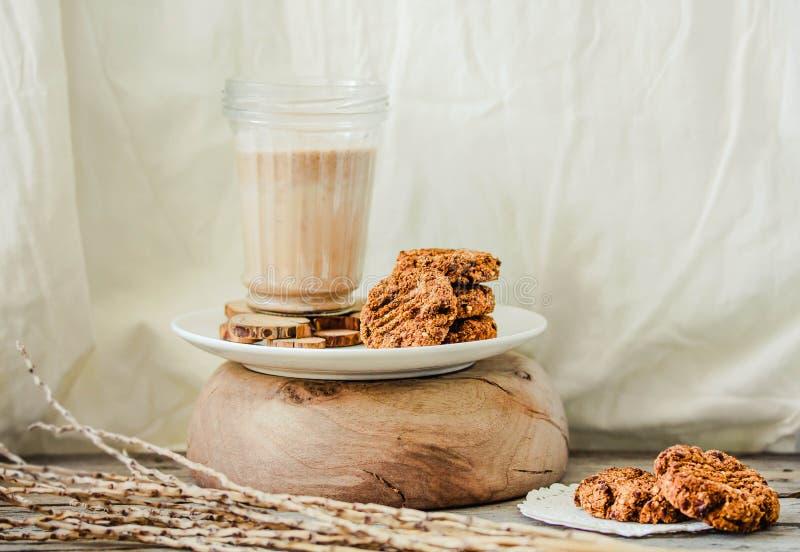 Galletas de mantequilla de la avena y de cacahuete con un vidrio de leche del c??amo del no-diario en un fondo de madera Concepto imagen de archivo