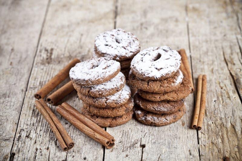 Galletas de microprocesador de chocolate cocidas frescas con los palillos del polvo y de canela del az?car en la tabla de madera imágenes de archivo libres de regalías